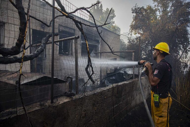 A firefighters extinguishing a fire at the moshav Giva'at Ye'arim. (Photo: Olivier Fitoussi/ Flash90)